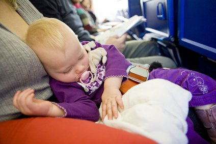 Schlafendes Baby mit Loop Belt auf Schoß im Flugzeug