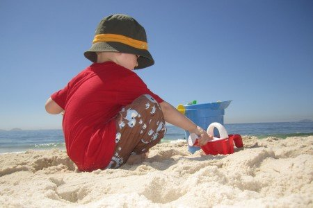 Sonnenbad ohne Konsequenzen: Kind mit Sonnenschutzbekleidung am Strand