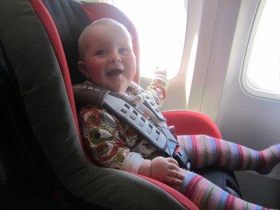 Zufriedenes Baby im Autokindersitz im Flugzeug