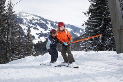 Ältere Kinder können schon das Snowboard testen