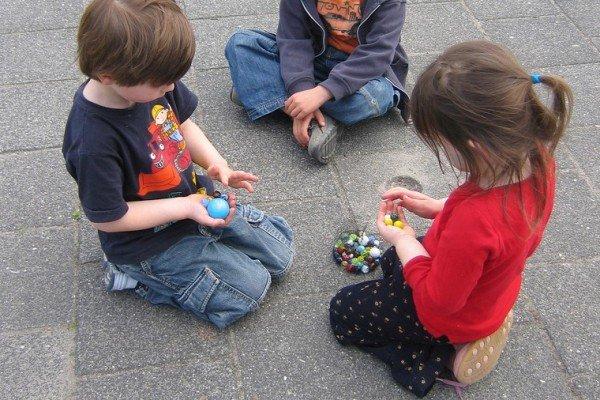 Mit Murmeln spielen macht allen Kindern Spaß