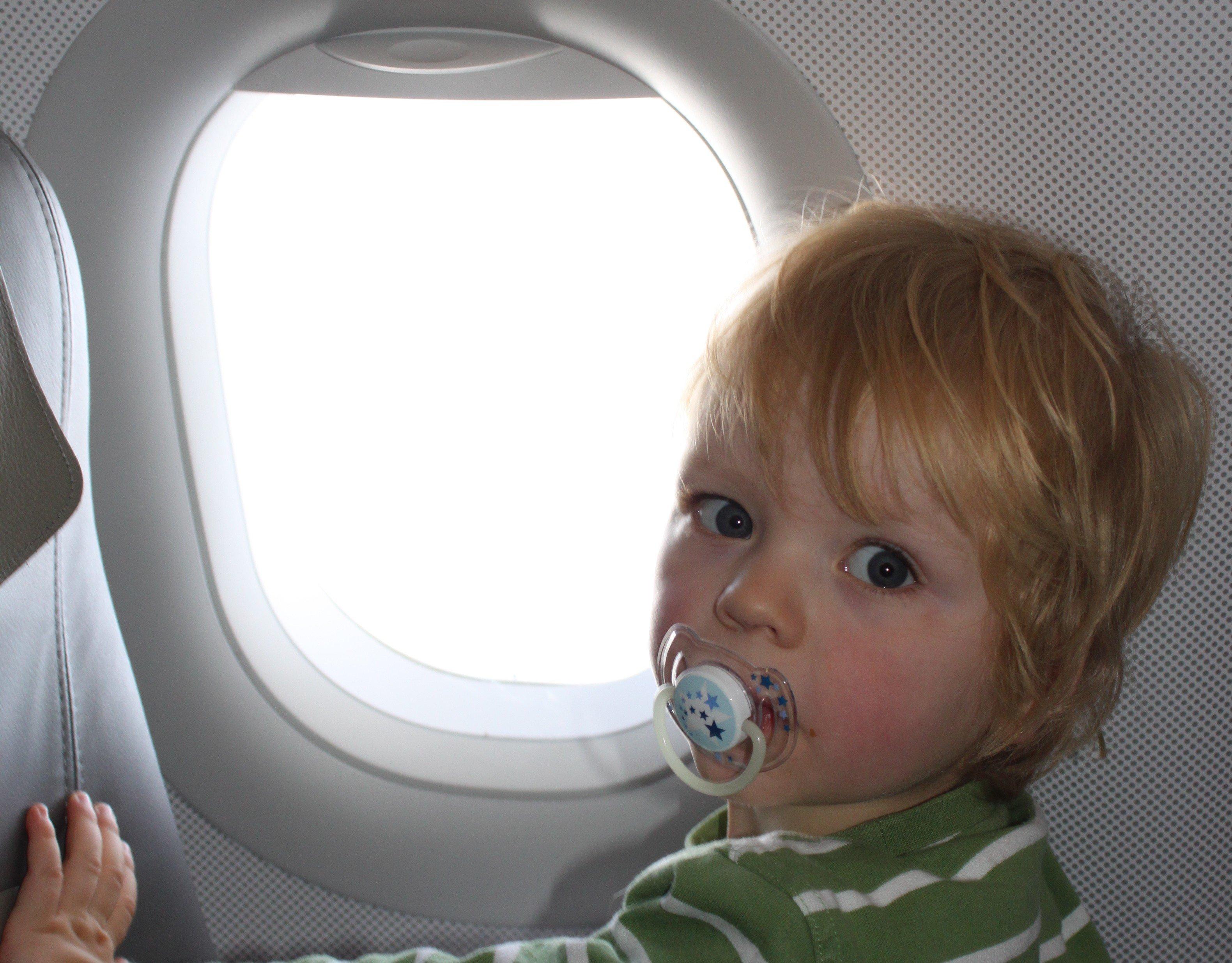 Kind im Flugzeug am Fenster